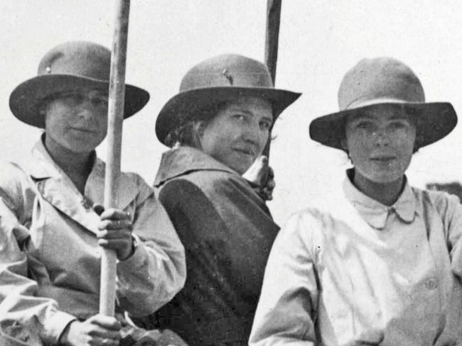 Black and white photograph of three women wearing hats with wide brims and overalls.
