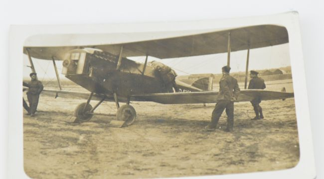 Black and white photograph of early bi-plane with three men standing near it.