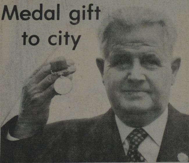 Newspaper black and white photograph of elderly man holding up a medal, with the headline 'Medal gift to city'
