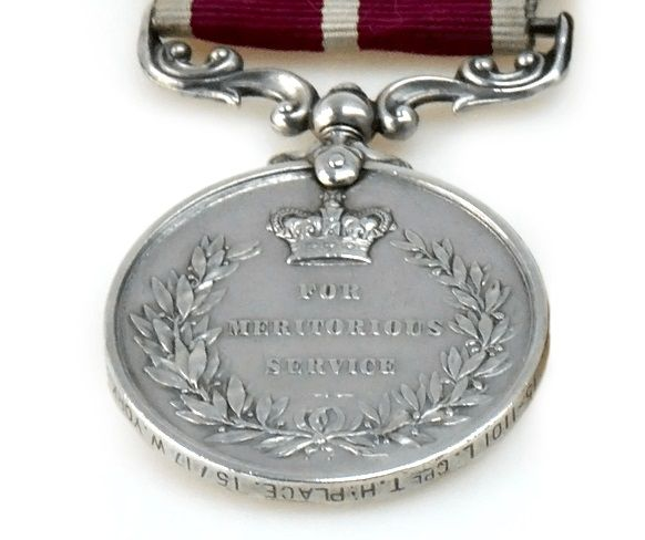 Silver coloured medal shows laurel wreath with the words 'For Meritorious Service' engraved in the middle.