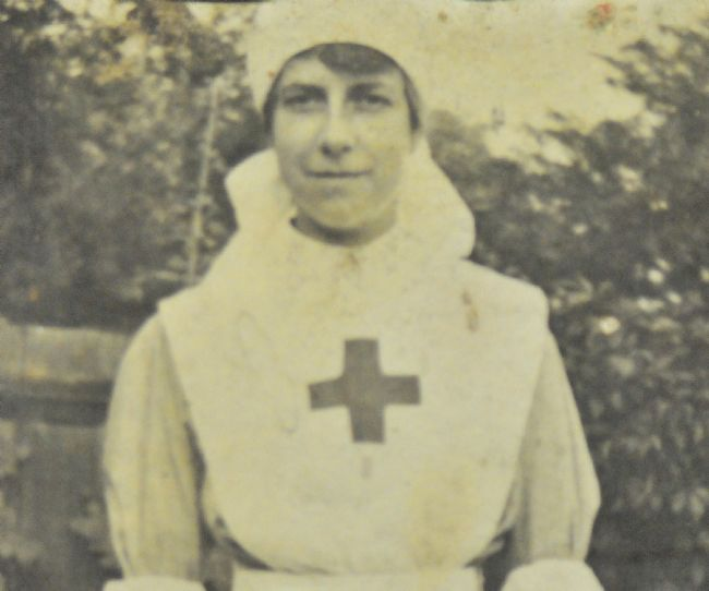 Phyllis Tessier wearing her WW1 nurses uniform of whtie apron with a cross on the front and white cap