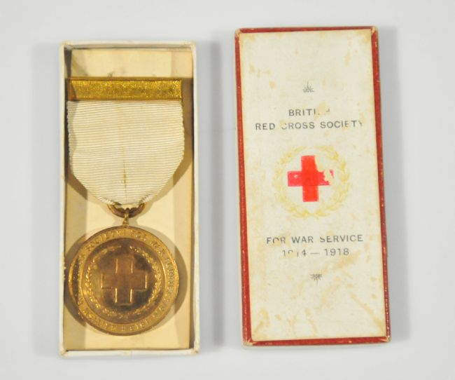 Gold WW1 Red Cross Medal, shown next to its box. The medal has a white ribbon