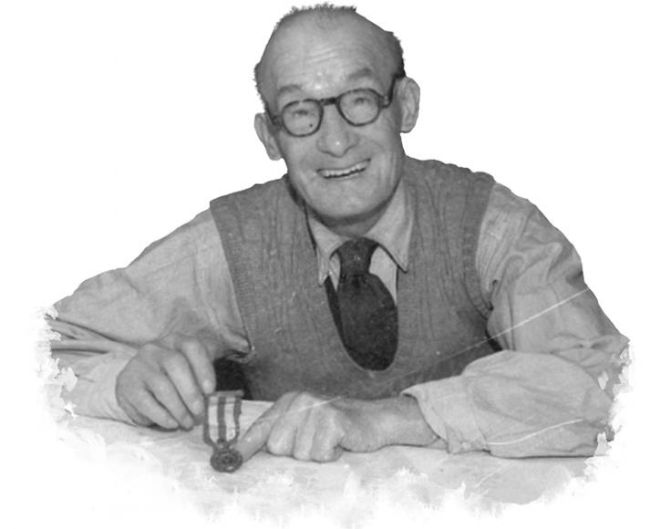 Black and white photograph of an elderly man holding a medal