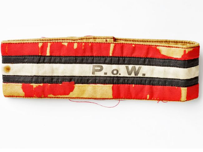 Fabric armband, originally red stripe top and bottom with two black stripes and a white stripe with 'POW' printed on.