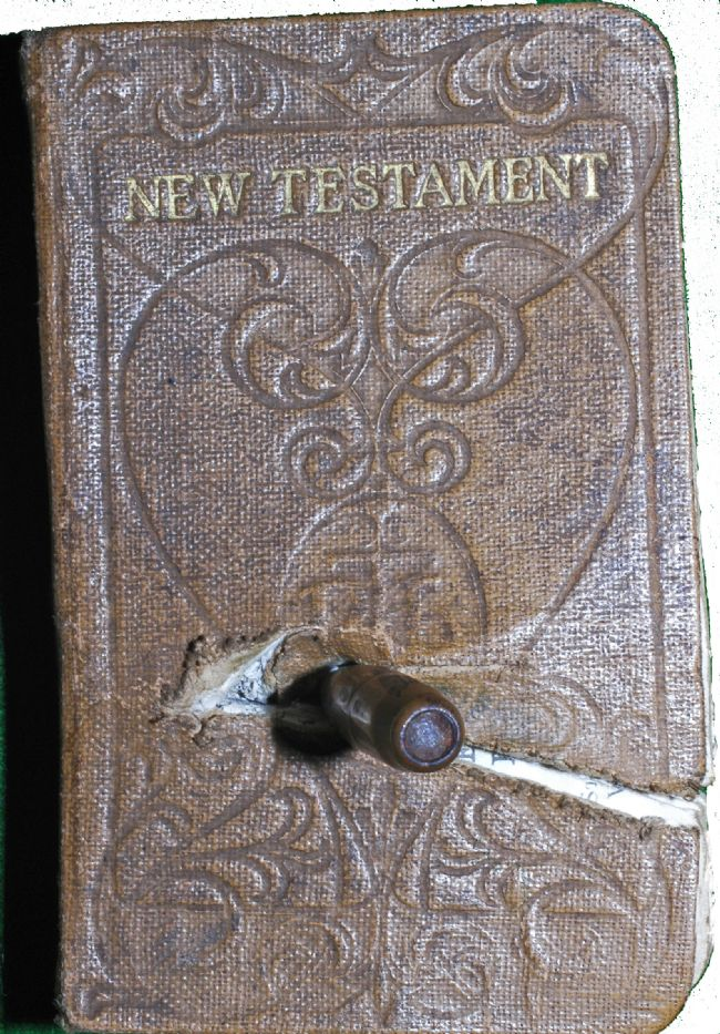 New Testament Bible  with a German bullet embedded in it
