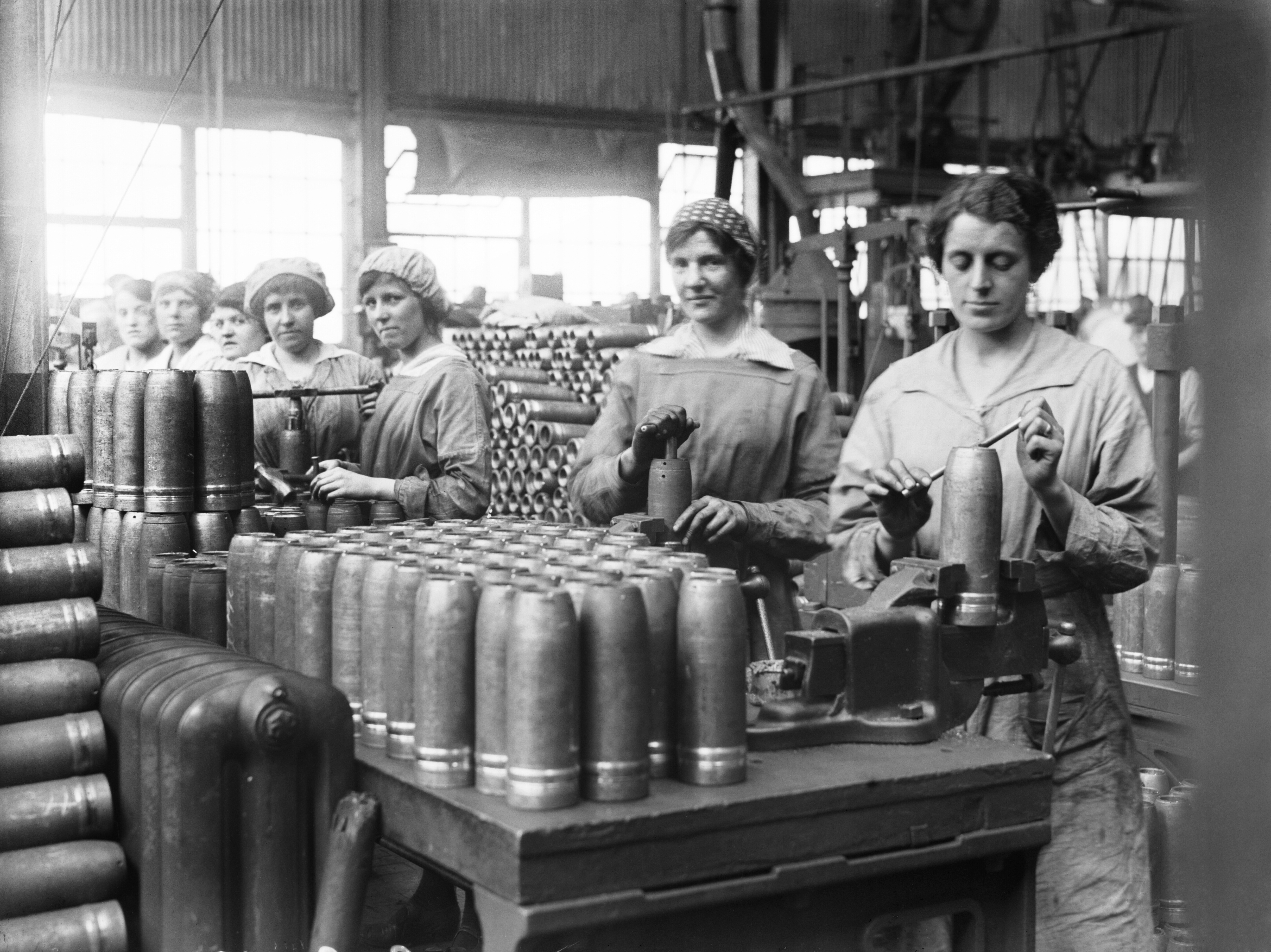 Black and white photograph showing women in a factory packing explosives into shell cases