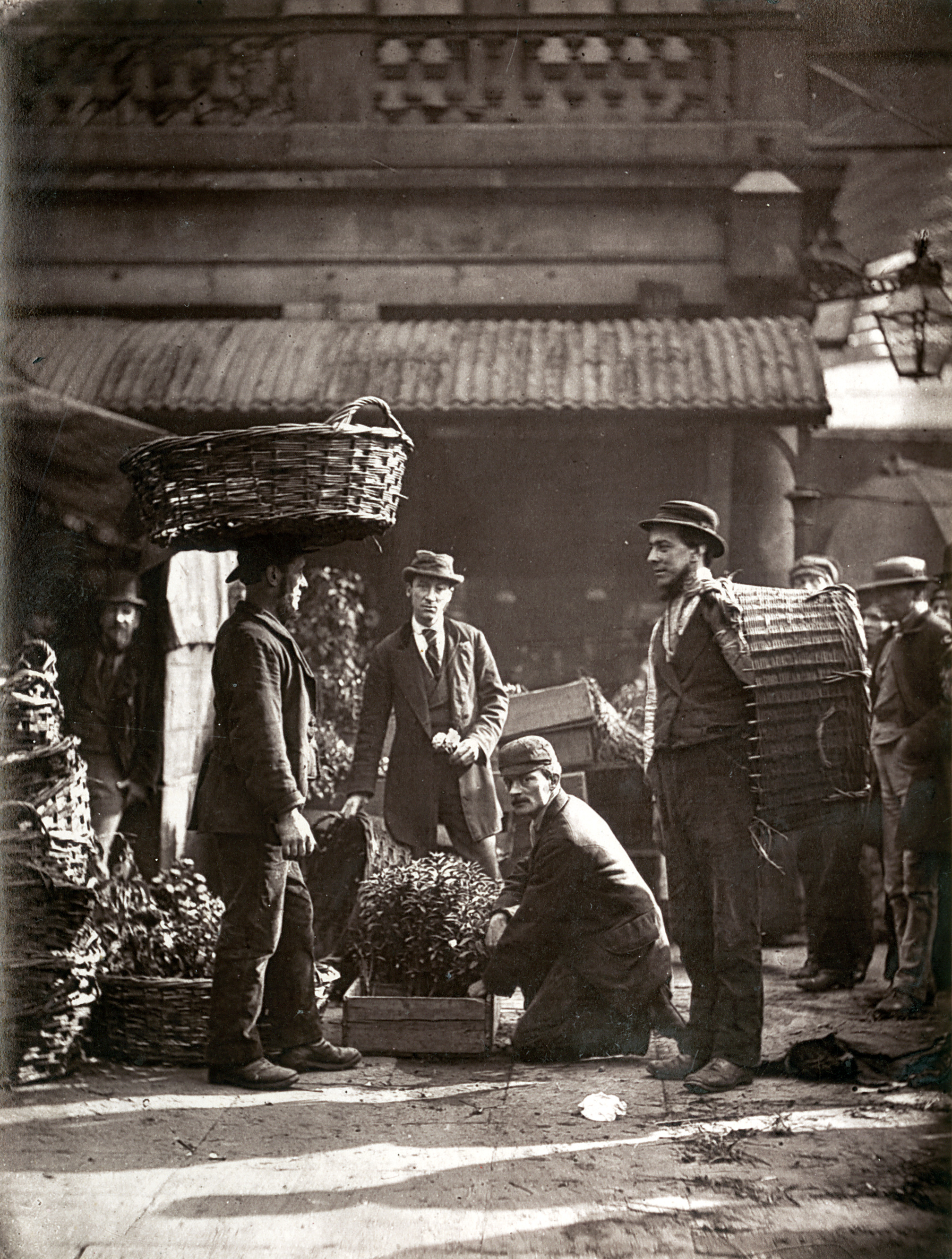 Black and white photograph of working men with large baskets, one with a basket on his head, in the market