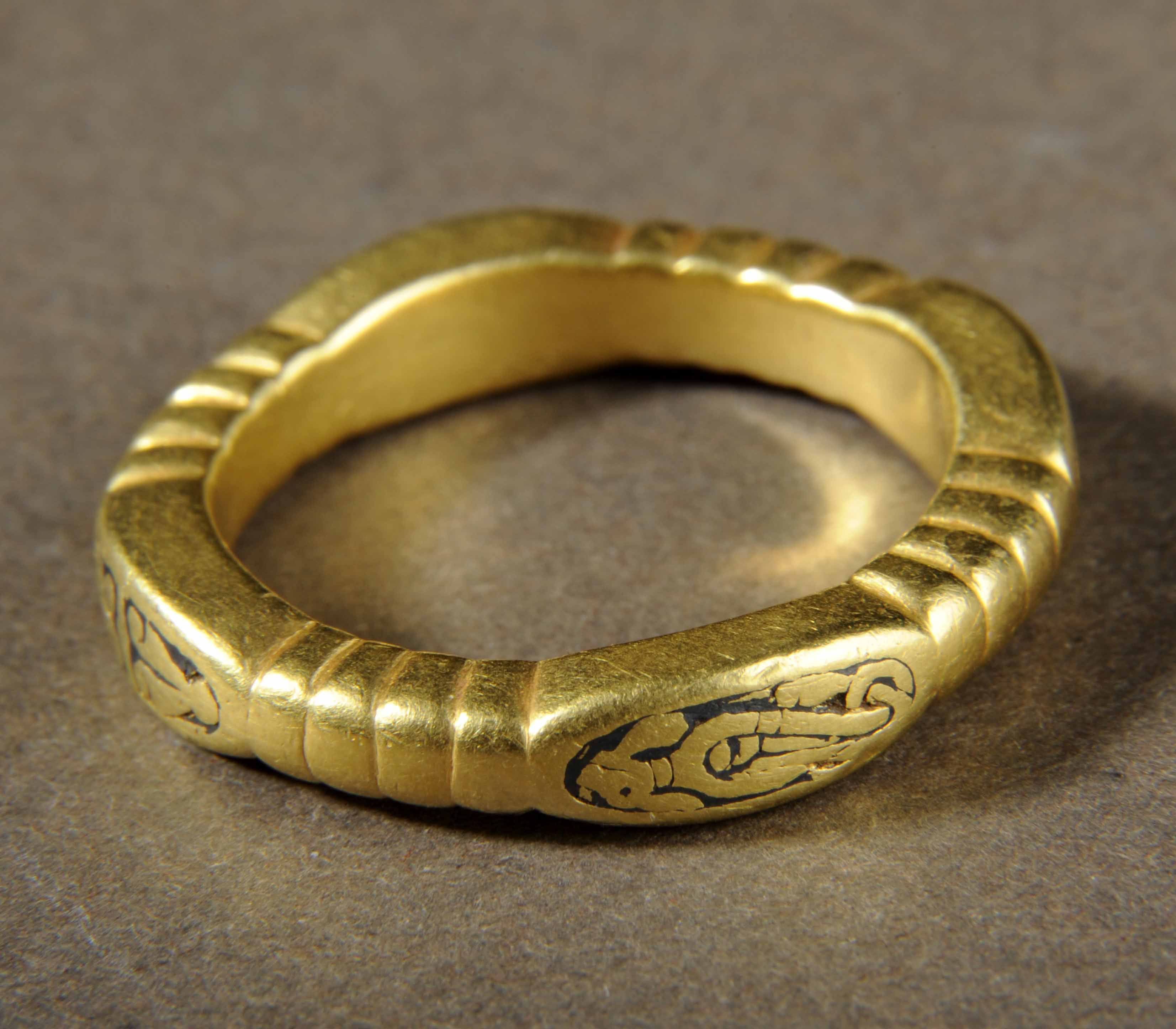 Gold ring with thick band in a rough square shape with a black design on each rounded corner.