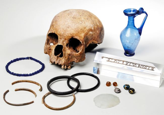 Roman skull missing the lower jaw, a blue glass jug, some bangles and beads.