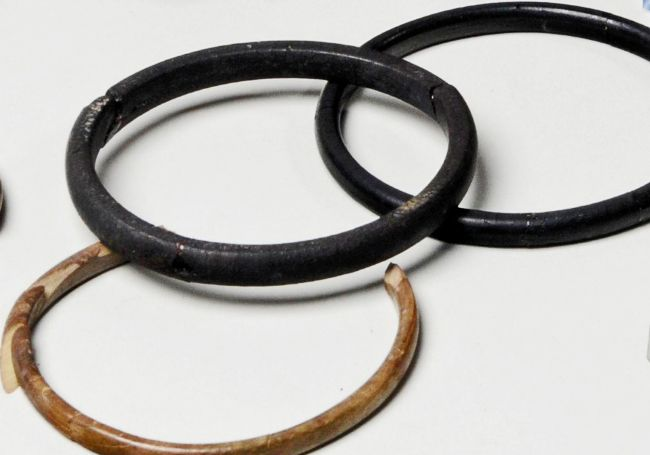 Close up of three bangles from the grave, including one ivory one.