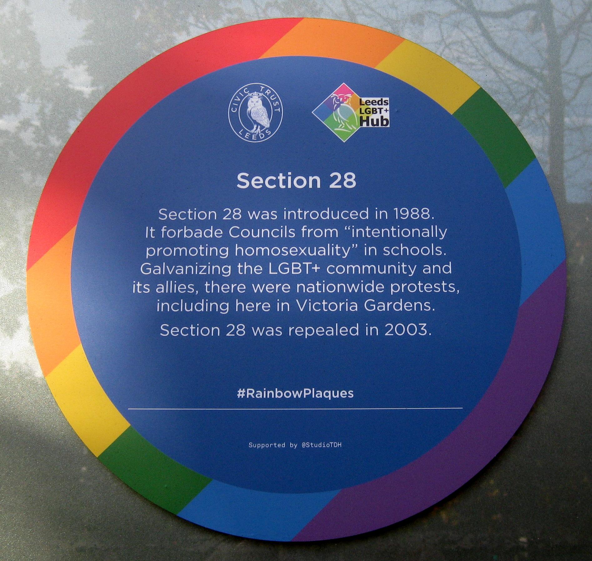 Colour photograph of a blue plaque with a rainbow edge