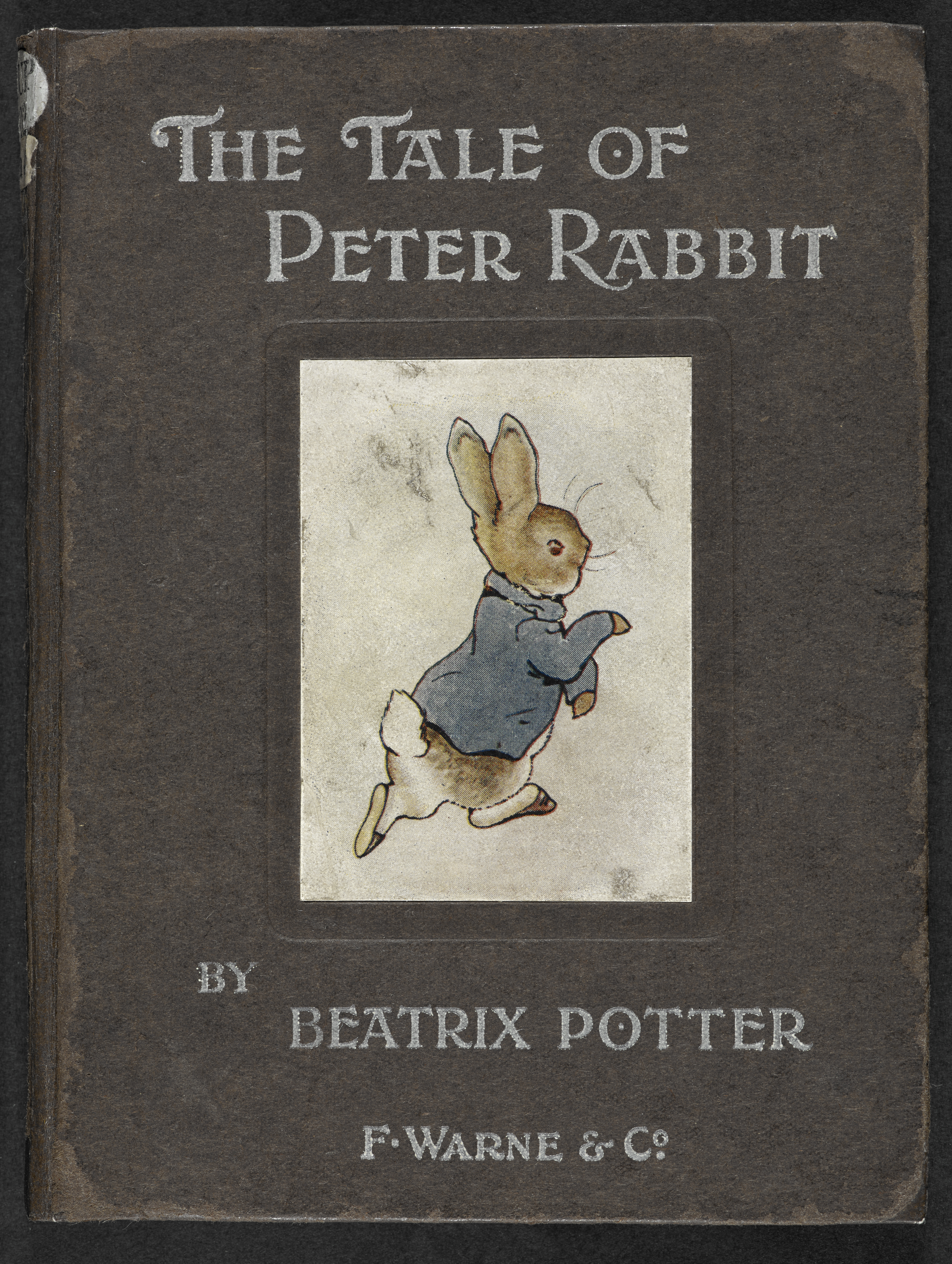 Front cover of The Tale of Peter Rabbit book, showing Peter walking upright on his back legs and wearing a blue coat.