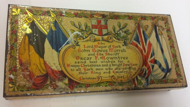 Tin decorated with flags and the inscription: 'The Lord Mayor of York, John Bowes Morrell and the Sheriff, Oscar F. Rowntree, send best wishes for a Happy Christmas and a bright New Year to all York men who are serving their King and Country. Christmas 1914'.