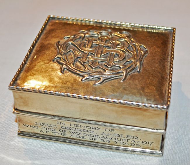 Square silver gilt box with raised design of a crown of thorns on the lid.