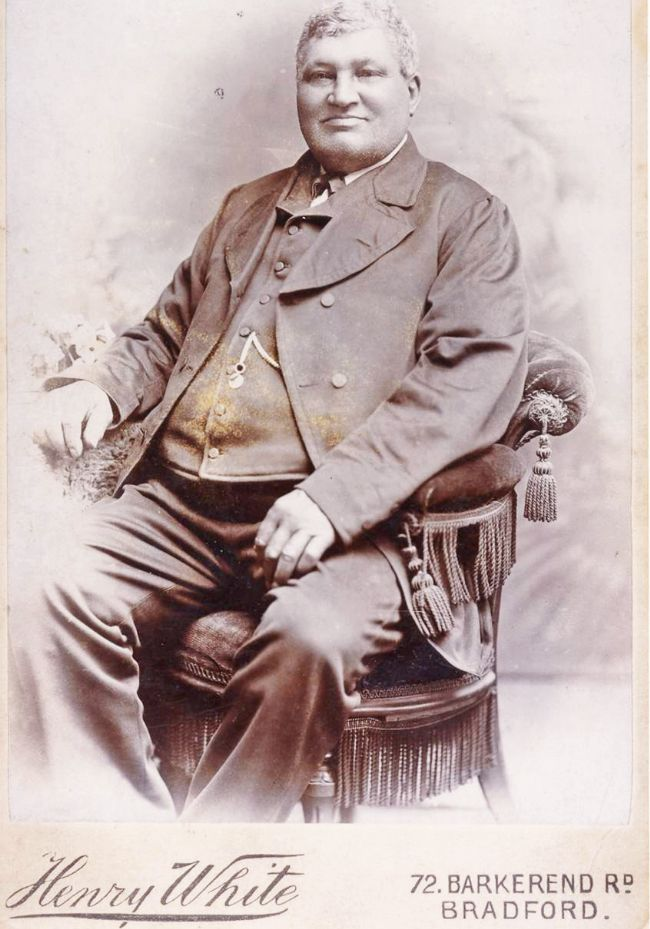 George Yorke sits on a velvet upholstered chair.  He is wearing a three piece suit, a tie and a watch chain.