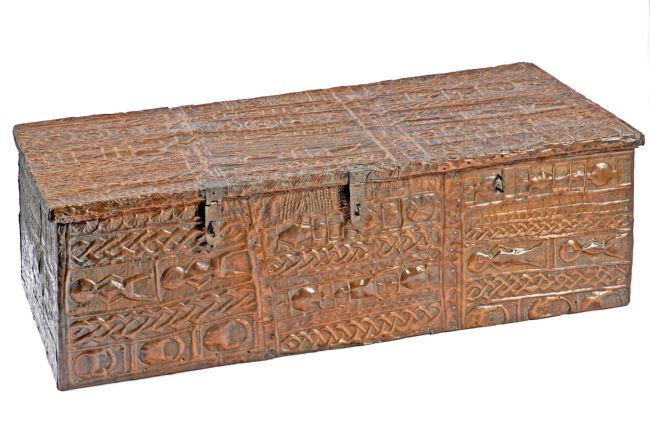 Asante treasure chest used for storing personal items.  It is covered in copper and embossed with designs of people and patterns.