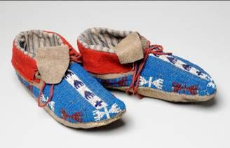 A pair of leather moccasins decorated with small glass beads.  The whole top surface of the shoes are beaded, mostly in a mid blue colour, with a white, red and black design along the edge and up the middle.