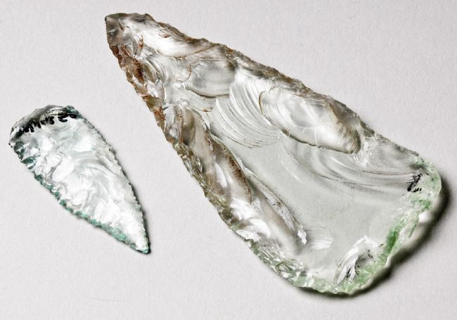 Two glass spearheads, one much bigger than the other.  Both are wider at one end and have been knapped to a point at the other.