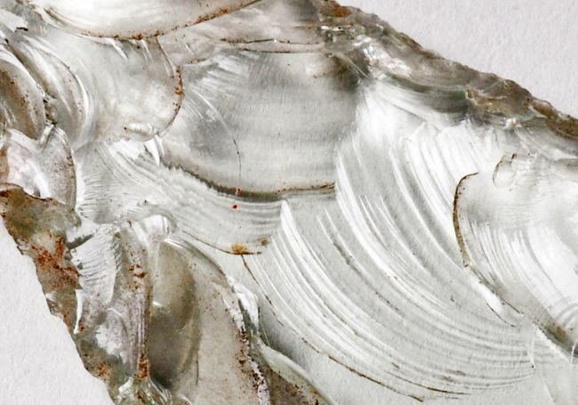 Close up shows the flake scars of parallel curved lines where flakes of glass have been removed.