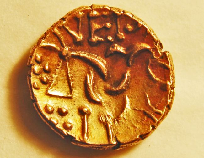 Small, concave gold going with ragged edges and raised inscriptions.
