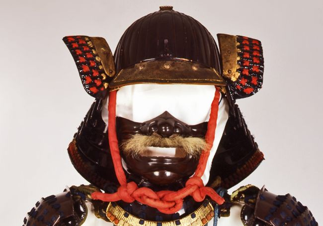 Helmet has a neck guard and bits sticking out each side by the visor.  It ties under the chine with a piece of red braid