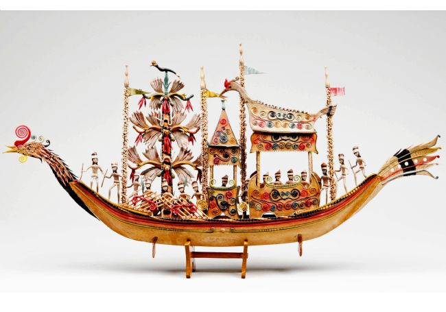 Model boat in the shape of a bird.  On board are many figures and three structures, two of which are canopies.  It is a colourful model, with yellow, red and blue the most prominent colours.