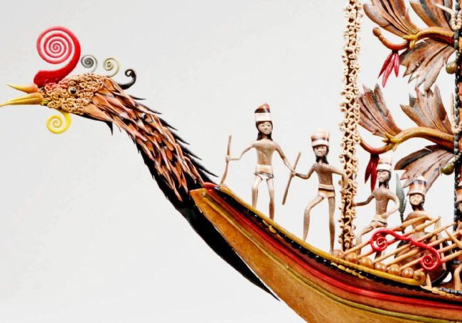 The prow of the boat is in the shape of a bird head and several figures wearing loin cloths and head dresses can be seen.