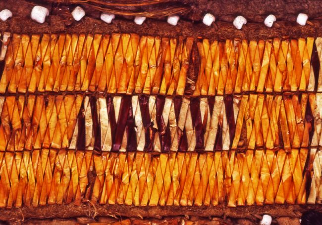 Detail shows different coloured material, maybe tree bark, stitched and folded into a design.