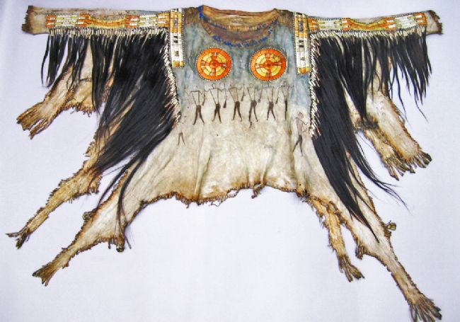 Shirt made from animal skin.  It features painted figures representing the many enemies that this warrior has overpowered, whilst the hoof prints symbolise the horses that he has captured and distributed among his people.