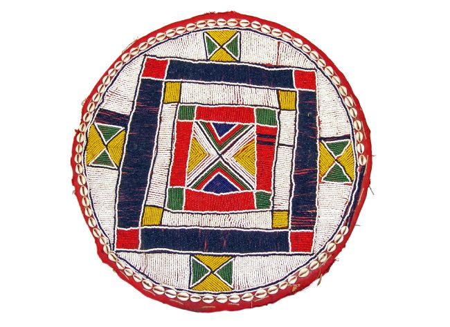 Circular beadwork mat in mostly white, with dark blue, red , yellow and green.  The design comprises mostly of different sized squares.