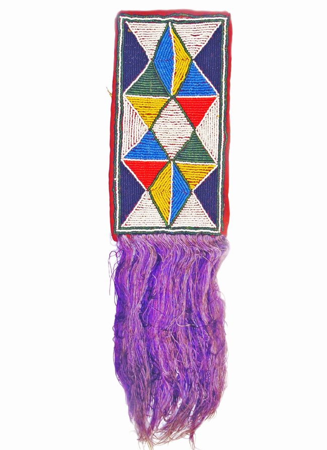 Rectangular beaded mat with purple tassles at one end.  Design is made up of triangles in light and dark blue, white, red, yellow and green beads.