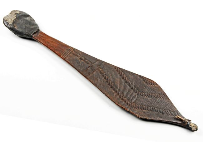 The spear thrower is shaped a bit like a western style dress tie.  The wide area of the  thrower is carved with patterns and the handle is covered by a kind of tree gum.