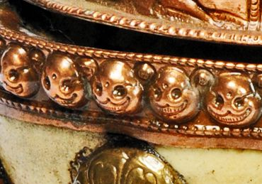 Detail of a Tibetan Skull cup showing a row of smaller gold skulls along the rim