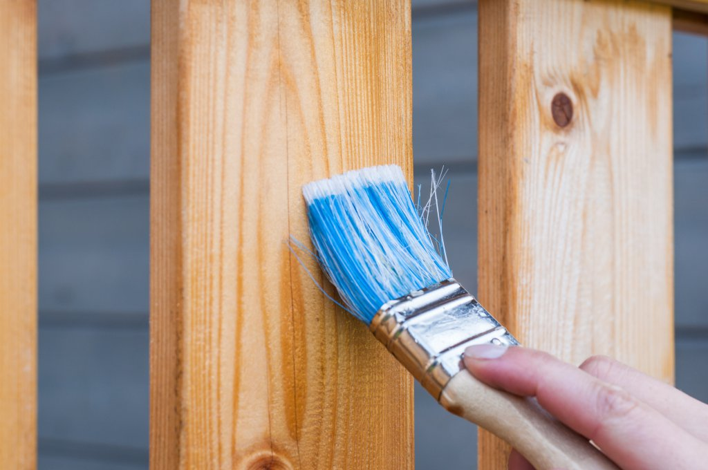 Paintbrush with blue paint painting wooden fence