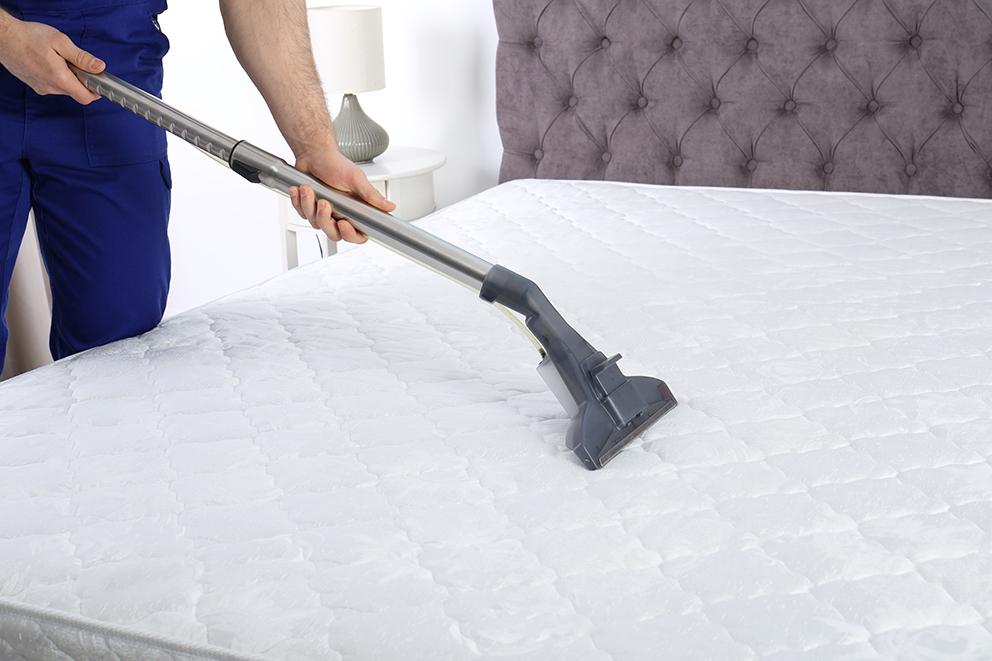 Man vacuuming a mattress