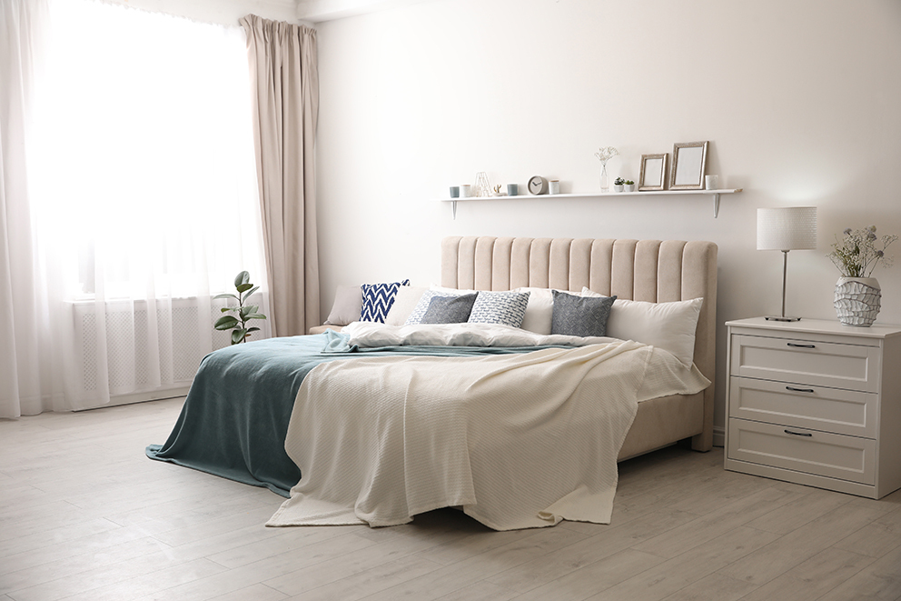 Bed in the centre of a light coloured bedroom