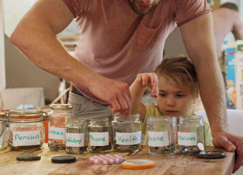 Dad and daughter money in jars darkened