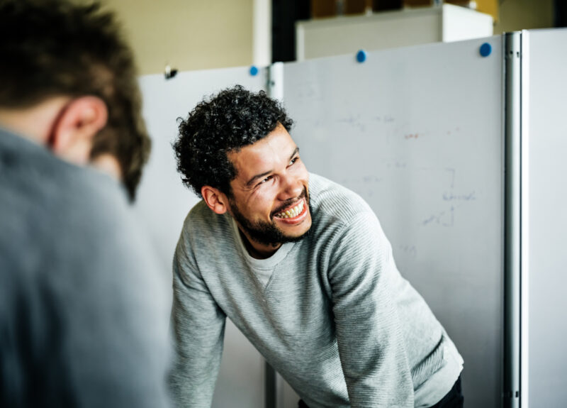 Man in grey jumper smiling off camera