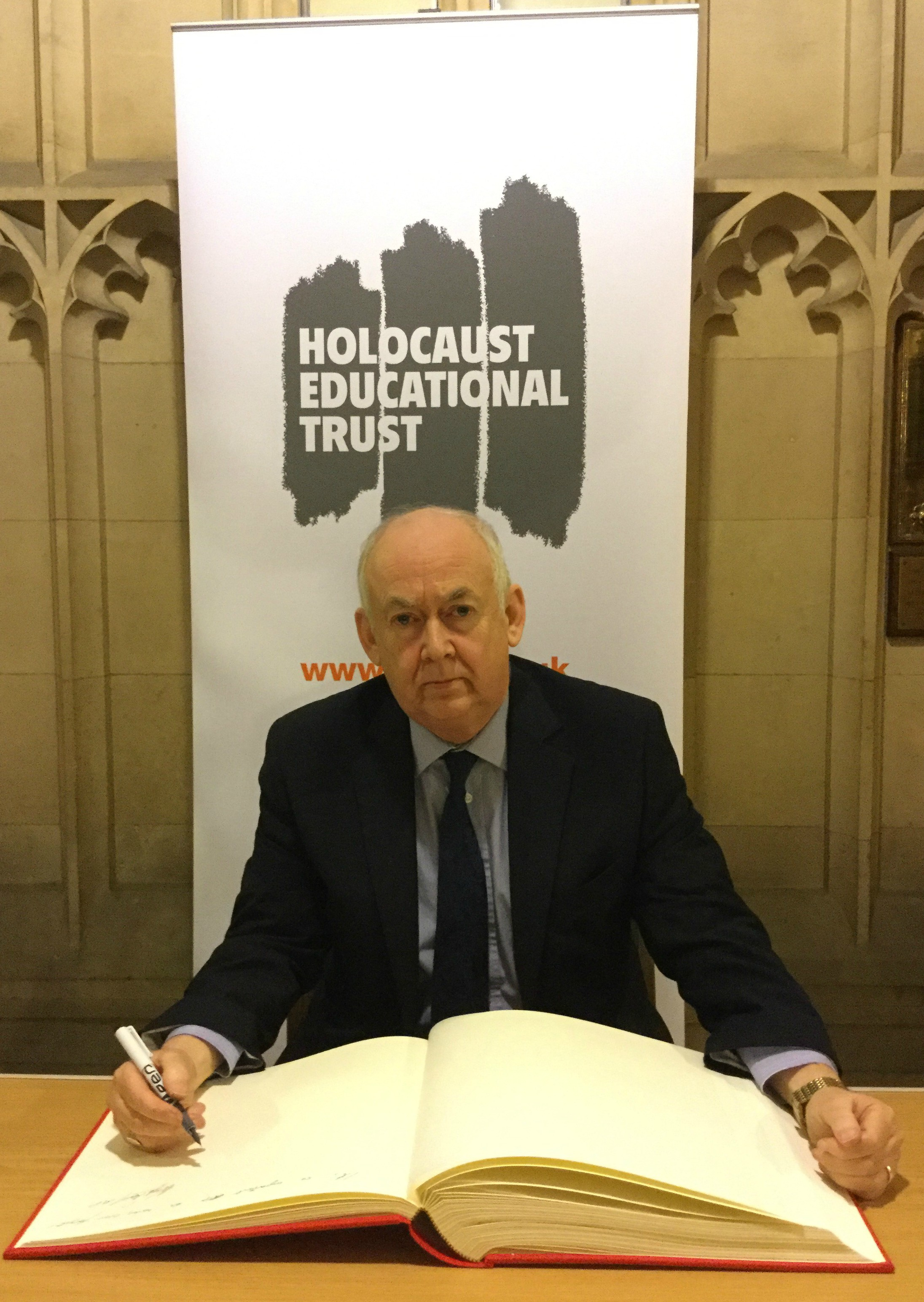 Wayne David signing the Holocaust Educational Trust's Book of Commitment