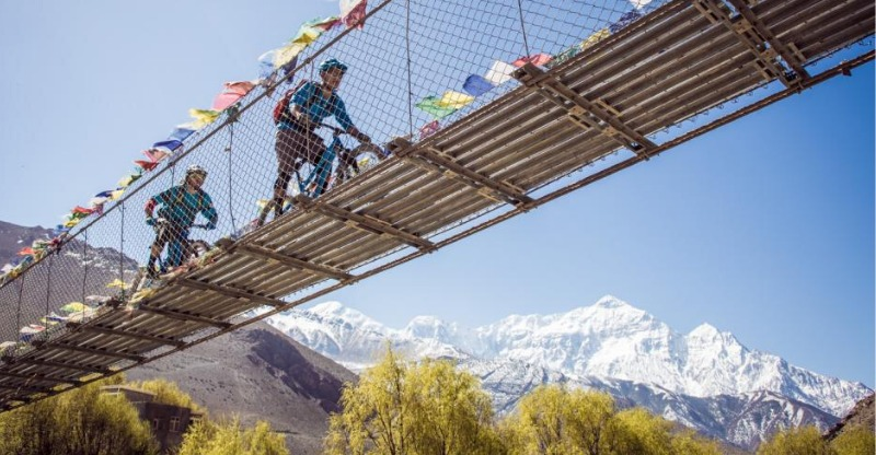 Mountain bikers on bridge in Nepal