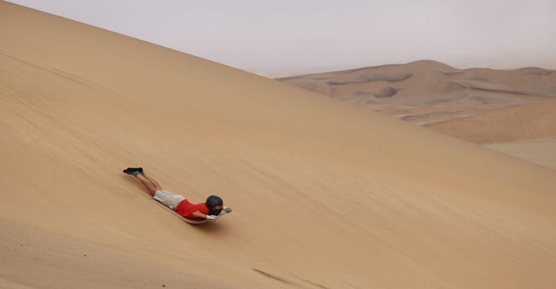 Guy Sandboarding in the Namib Desert