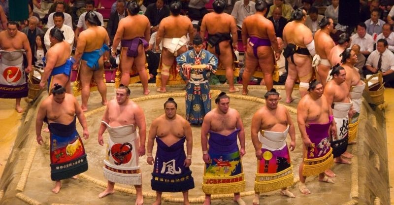 Competitors in ring and bright robes at Grand Sumo Wrestling Tournament