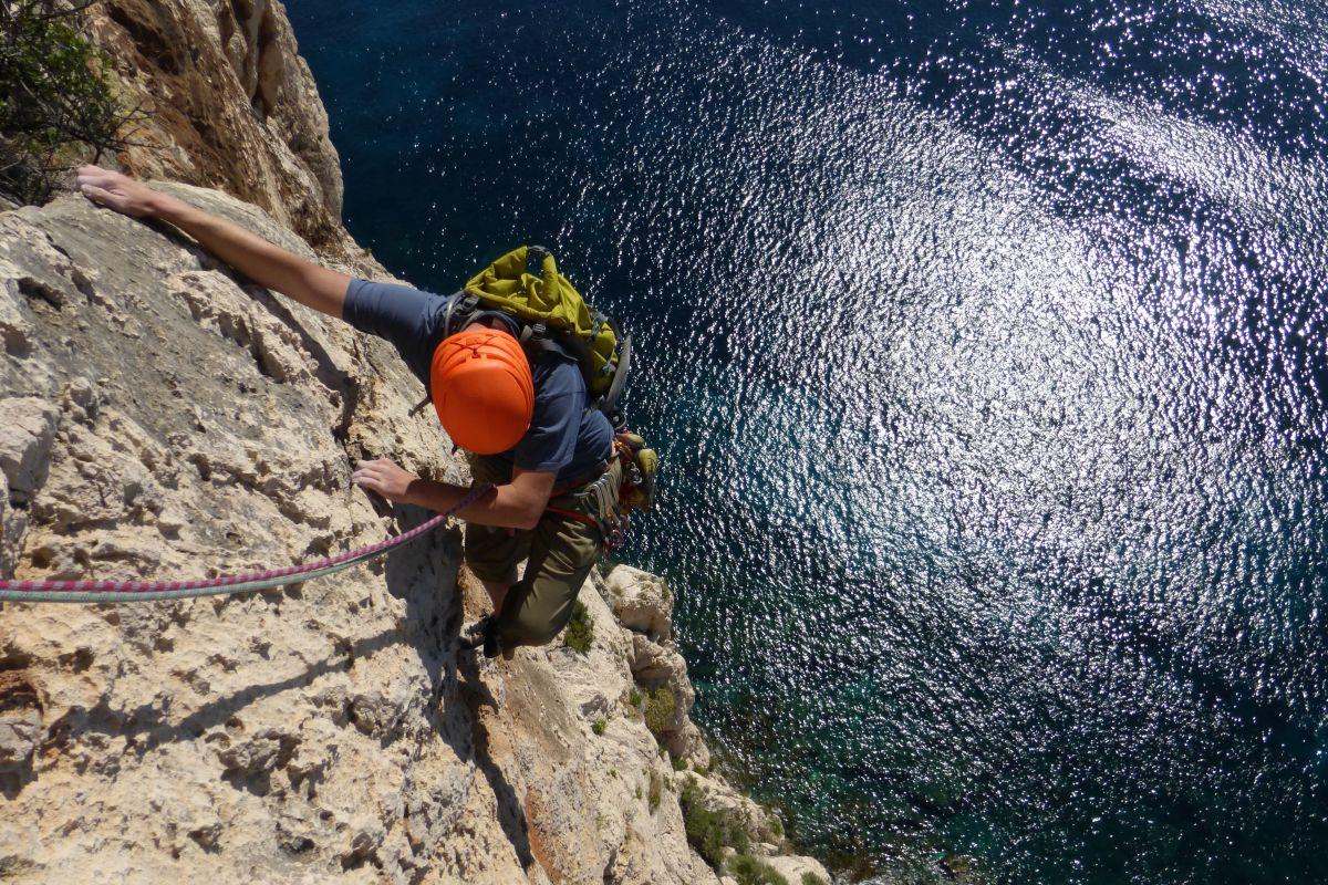 Man rock climbing in Sardinia looking down at sea