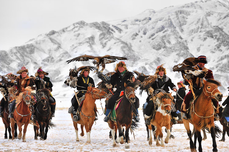Men riding horses at Golden Eagle Festival Mongolia