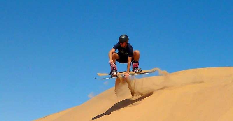 Man Sandboarding in the Namib Desert