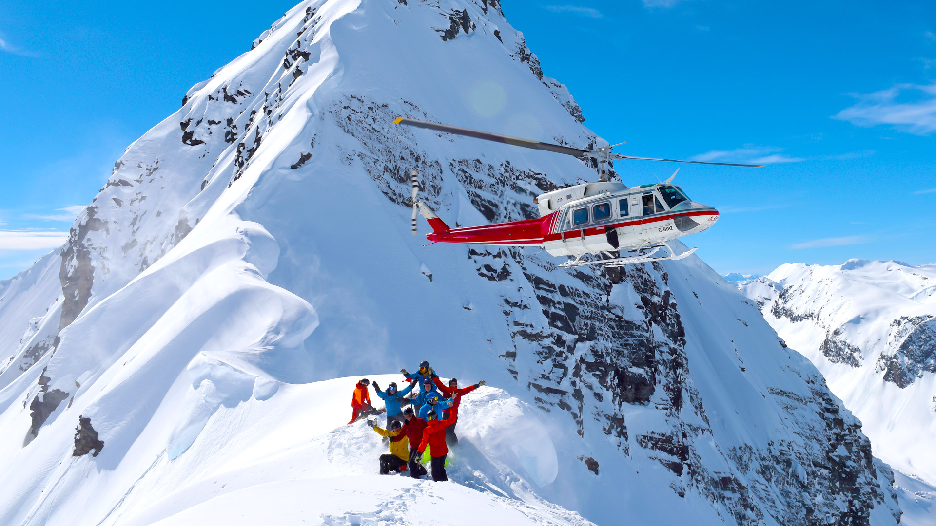 heli-skiing group waving to helicopter on mountain in canada