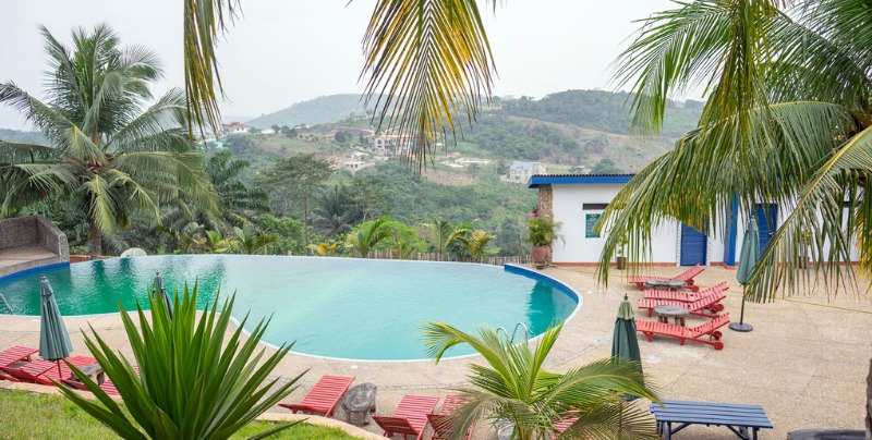Hillburi mountain escape pool with palm trees and loungers