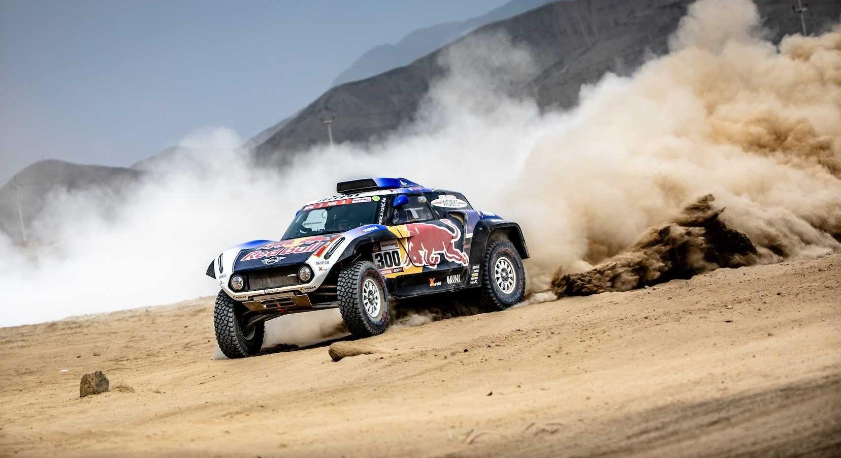 dakar rally car racing across sand dunes