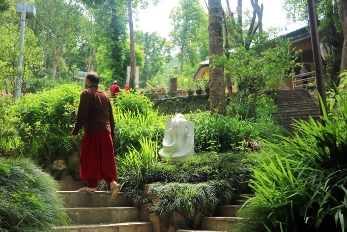 Man walking through garden at Osho Meditation Retreat