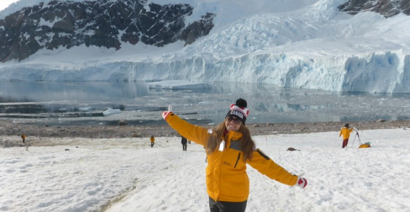 woman smiling in front of snowy glacier on antarctica adventure
